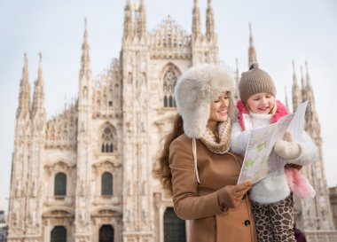 Mother and daughter looking on map while standing near Duomo