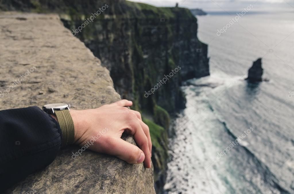 holding tight at the edge of a cliff