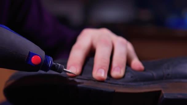 Ein Schuhmacher schneidet die Sohle eines Schuhs mit einem automatischen Schuhschneider. Die Hände eines Schusters bei der Arbeit.