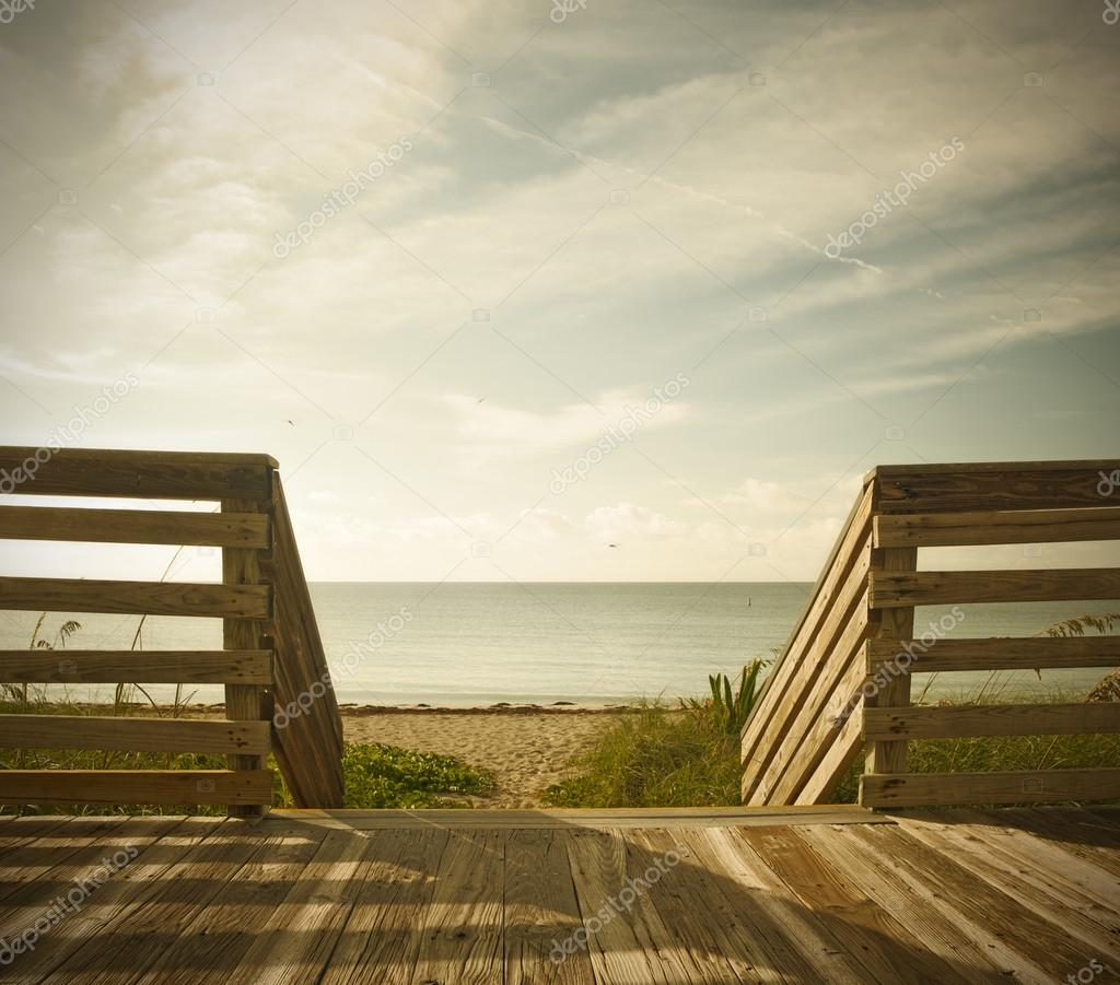 Wooden deck with fence overlooking the ocean and the beach