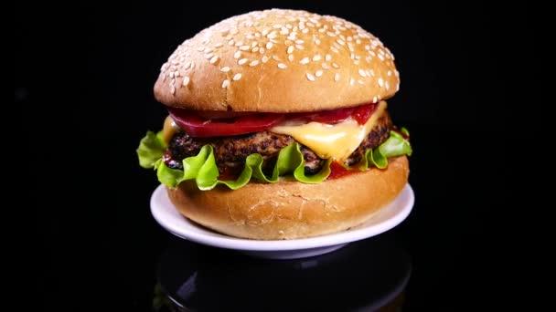 Předkrm burger na černém pozadí. Vynikající fast food. Hamburger a cheeseburger se salátem a sýrovou kotletou