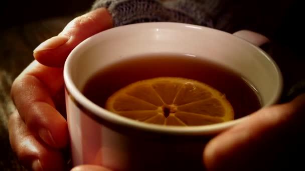 Teplý čaj s citronem. Zahřejte si dlaně dlaněmi na hrnek s teplým nápojem. Chladná léčba.