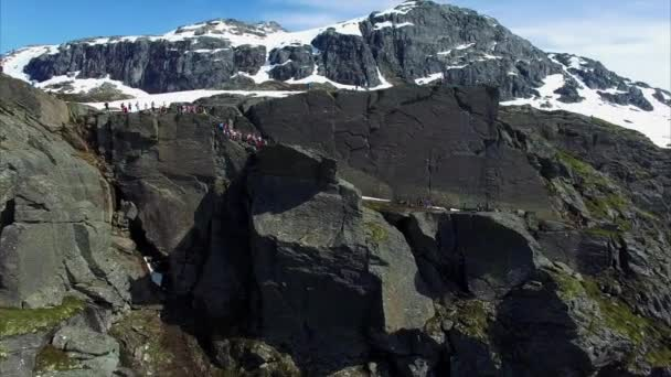 Aerial footage of famous Trolltunga rock in Norway with crowds of people gathered around