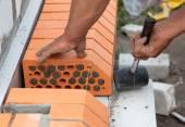 Tvůrce klade cihly v cementové malty