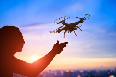 man playing with  drone at  sunset