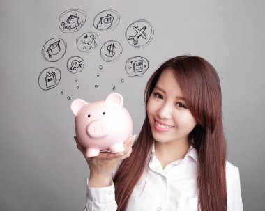 woman holding pink piggy bank