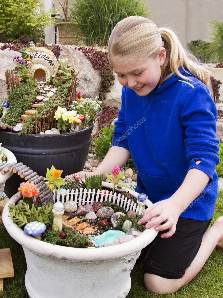 Young girl helping to make fairy garden in a flower pot