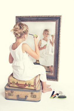 Child or young girl putting on make-up while looking at herself