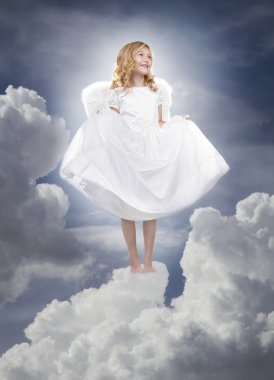 Child angel standing on fluffy clouds in the sky