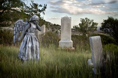 Girl wearing an angel costume in an old grave yard