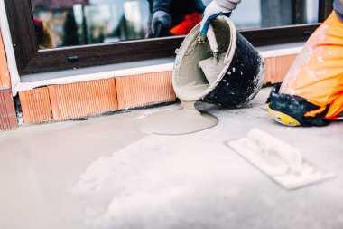 industrial worker on construction site pouring sealant from bucket for waterproofing cement