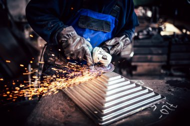 Professional worker using angle grinder for cutting and finishing steel