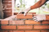Fotografia operaio di costruzione professionale che pone i mattoni e la costruzione di barbecue nel sito industriale. Dettaglio della mano mattoni di regolazione