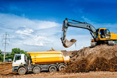 Fotografie Industrial truck loader excavator and bulldozer moving earth and unloading into a dumper truck