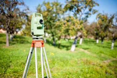 Total station surveying and measuring engineering equipment at work in garden or forest