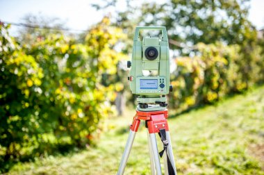 Surveyor engineering equipment with theodolite and total station in a garden at a construction site