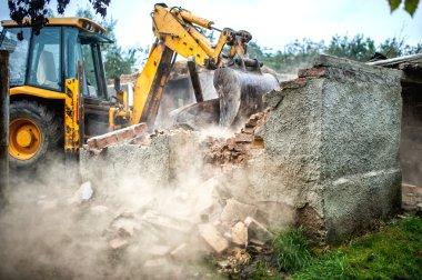 bulldozer demolishing concrete brick walls of small building