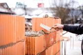 Fotografia Muratore muratore costruzione di pareti con mattoni freschi e strumenti