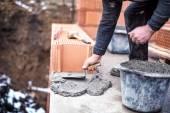 Fotografia operaio di costruzione utilizzando la cazzuola e cemento per linstallazione di muratura