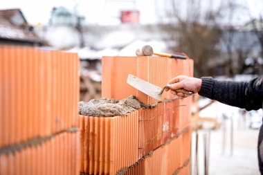 Construction bricklayer worker building walls with fresh bricks and tools