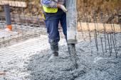 stavba, stavební dělník vylévající cement nebo beton čerpadlo trubice