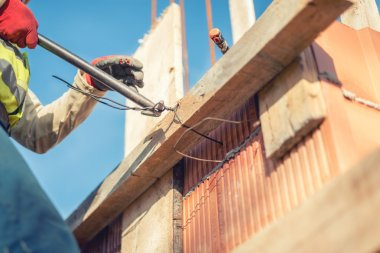 Details of infrastructure - Construction worker hands securing wooden boards with wire rod for reinforcement of concrete