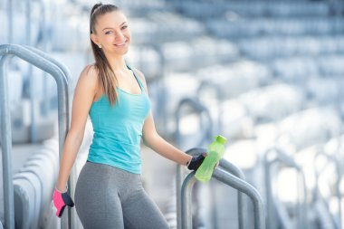 Fitness concept - sexy woman drinking water during workout and training. Cross fit workout on stairs, squats and exercises