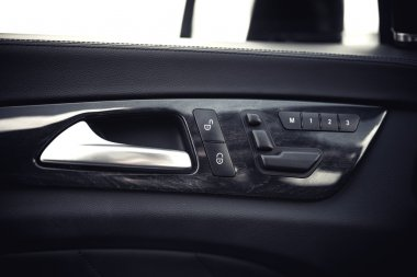 Modern car interior details. Door handle and electronic memory for the chairs.