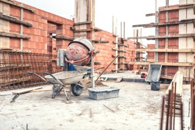 Cement mixer machine at construction site, tools, wheelbarrow, sand and bricks at new house building.