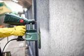 Fotografie Arbeiter Malerei Mauer mit grauer Farbe mit einer professionellen Spritzpistole. Mann Malerei Mauer mit Schutzhandschuhe