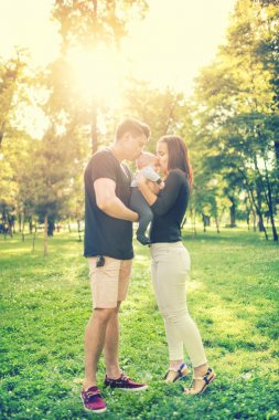 Happy familiy in park, mother and father holding and kissing a few months old son, kid. Infant portrait and happy family concept in park
