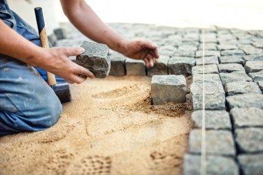 """Картина, постер, плакат, фотообои """"строитель размещения каменной плитки в песке на тротуар, терраса. Работник размещения гранита булыжник тротуар на местном террасе"""", артикул 80052084"""