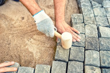 Construction worker installing stone blocks, creating pavement on road, sidewalk or path.