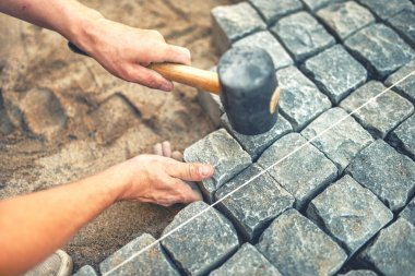 Close-up of construction worker installing and laying pavement stones on terrace, road or sidewalk. Worker using stones and rubber hammer to build stone sidewalk