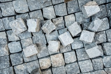 Road pavement, stone blocks and construction tools. Construction worker laying cobblestone pavement stones