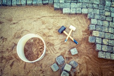 Construction of pavement details, cobblestone pavement, stone blocks and rubber hammers on construction site
