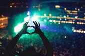 Fotografie Ruce na koncertě, milující umělec a na festivalu ve tvaru srdce. Hudební koncert světly a siluetu člověka těší na koncert