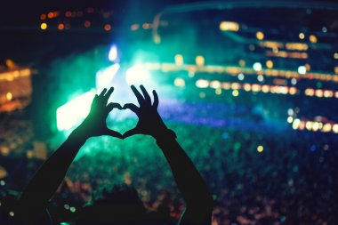 Heart shaped hands at concert, loving the artist and the festival. Music concert with lights and silhouette of a man enjoying the concert stock vector