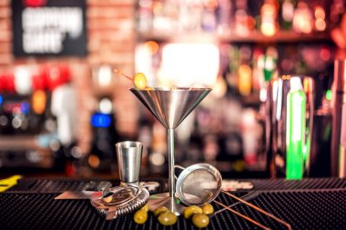 alcoholic drink on bar counter. Dry martini with ice and olives, served cold in restaurant, bar or pub.