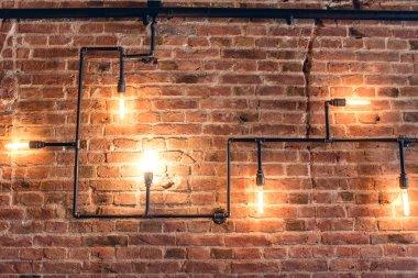 """Картина, постер, плакат, фотообои """"Дизайн интерьера старинные стены. Деревенский дизайн, кирпичная стена с лампы и трубки, низкая освещенный бар интерьер"""", артикул 86644036"""