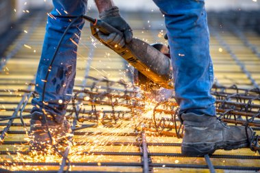industrial worker cutting steel, sawing reinforced bars using angle grinder mitre saw