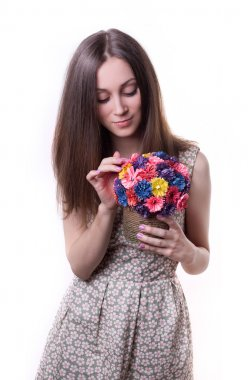 Pretty sweet young brunette girl with expressive eyes holding handmade colorful bouquet of flowers from paper isolated on white. tenderness. youth. gift. surprise. emotion.