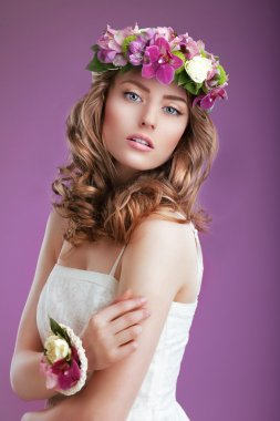Exquisite Woman with Wreath of Flowers. Elegant Lady with Frizzy Hair