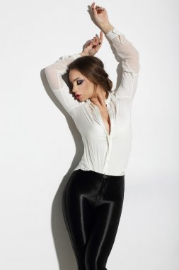 Aspiration. Seductive Woman in White Blouse with Hands Raised
