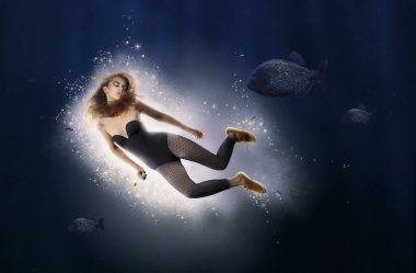 Creativity. Fantasy. Woman is Diving in Water