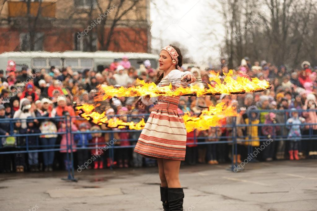Orel, Russia - March 13, 2016: Maslenitsa, Pancake festival. Fire dancer girl in Russian clothes performing for crowd selective focus stock vector