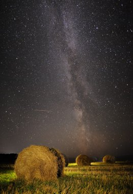 Milky Way and wheat field with haystacks