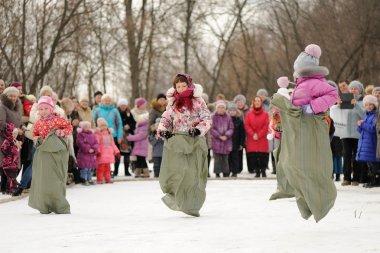 Little girls sack-racing during winter Maslenitsa carnival in Ru