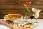 Sýr koláč s červeným vínem a červené tulipány na dřevěné pozadí