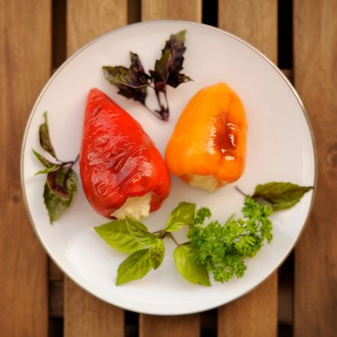Red and yellow bell peppers stuffed with cheese garnished with b
